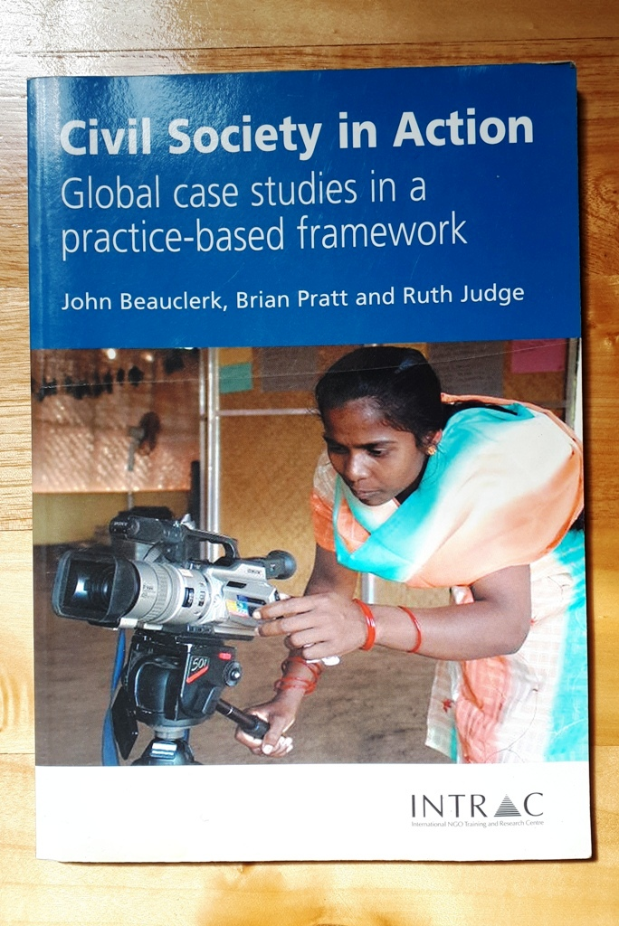 "Book cover for ""Civil Socety in Action"" showing a South Asian woman with a video camera."