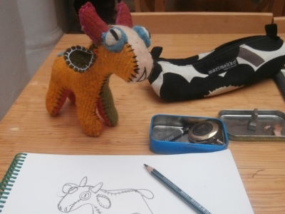 "A toy felt bull being drawn ""San Cristobal"", Mexico #SancrisEnColores"